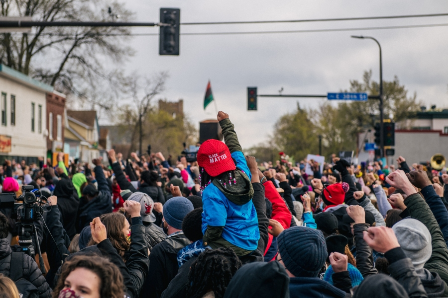 A child sits atop an adult's shoulders during a gathering at the intersection of 38th Street and Chicago Avenue in Minneapolis following the guilty verdict in Derek Chauvin's murder trial on April 20, 2021. (Brandon Bell / Getty Images)