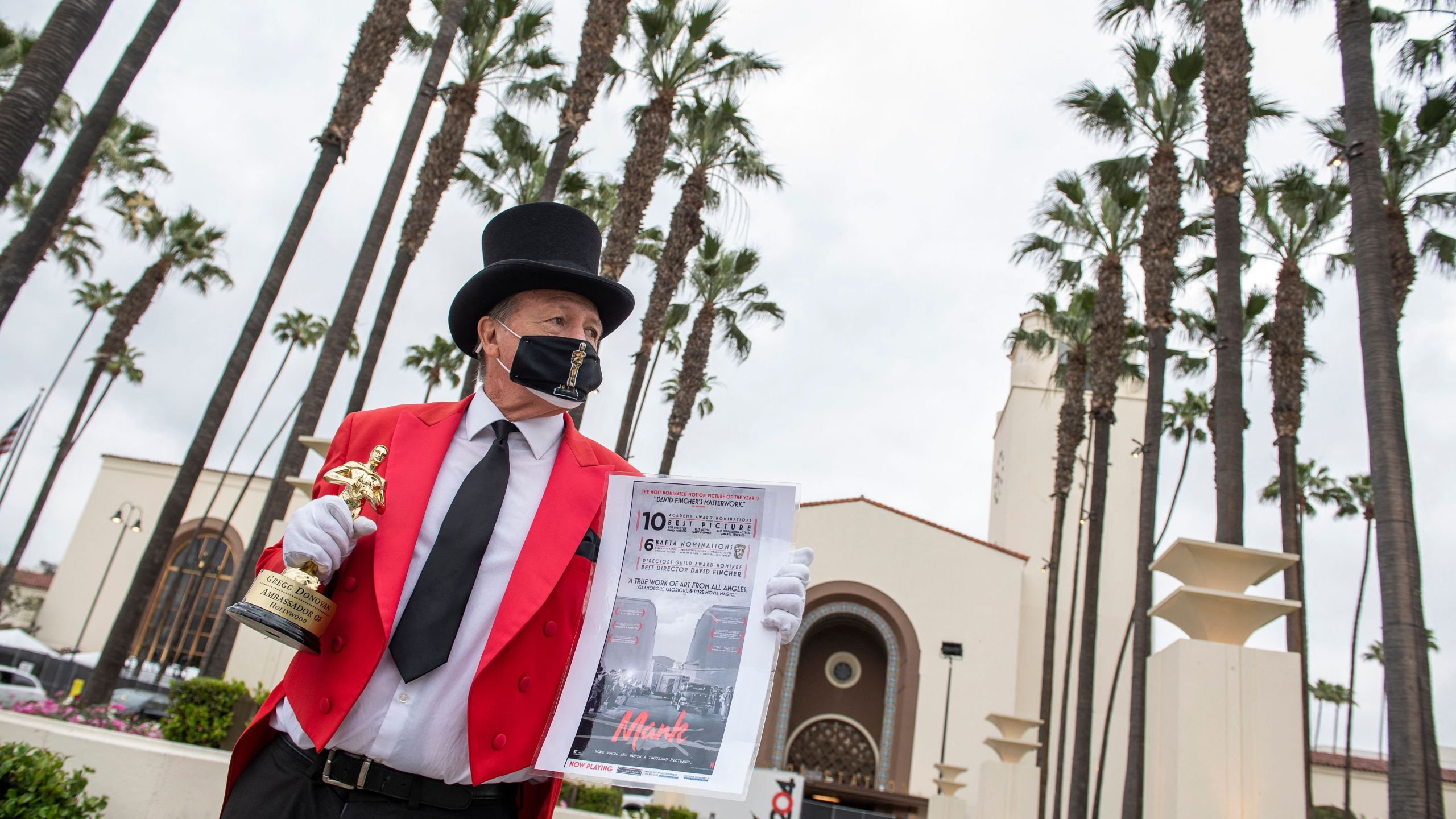 Gregg Donovan holds a fake Oscar statuette and a poster of one of the movies he believes will be a winner in front of Union Station during preparations for the 93rd Academy Awards in Los Angeles, California on April 23, 2021. (Valerie Macon/AFP via Getty Images)