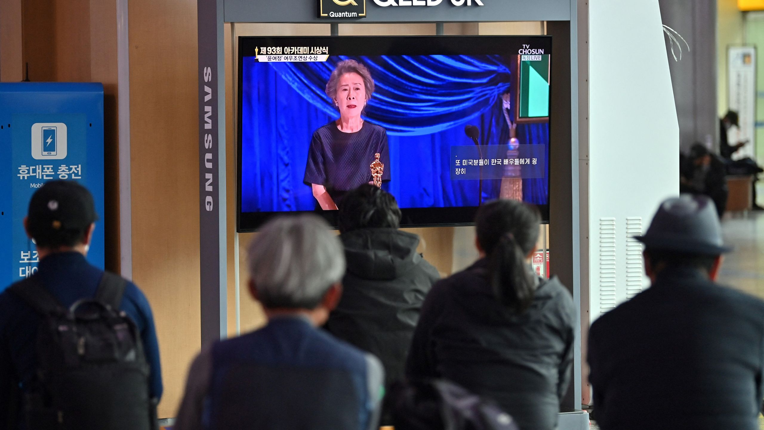 People watch a television screen broadcasting live footage of South Korea's first Oscar-winning actress Youn Yuh-jung speaking at the 93rd Academy Awards ceremony held in Los Angeles, at Seoul railway station in Seoul on April 26, 2021. (JUNG YEON-JE/AFP via Getty Images)