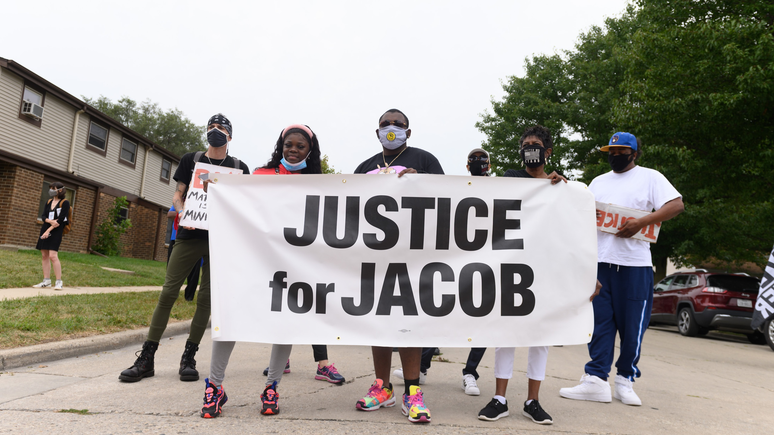 "Protesters hold a banner during a community celebration and call for justice for Jacob Blake as grassroots group MoveOn flies an airplane banner and drives a mobile billboard calling on voters to ""Reject Trump's Violence,"" in response to Donald Trump's visit on Sept. 1, 2020 in Kenosha, Wisconsin. (Daniel Boczarski/Getty Images for MoveOn)"