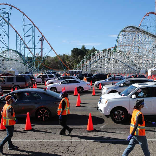 Volunteers walk past people who have received their COVID-19 vaccinations at the mass drive-thru vaccination site at Six Flags Magic Mountain on Feb. 2, 2020 in Valencia. (Mario Tama/Getty Images)