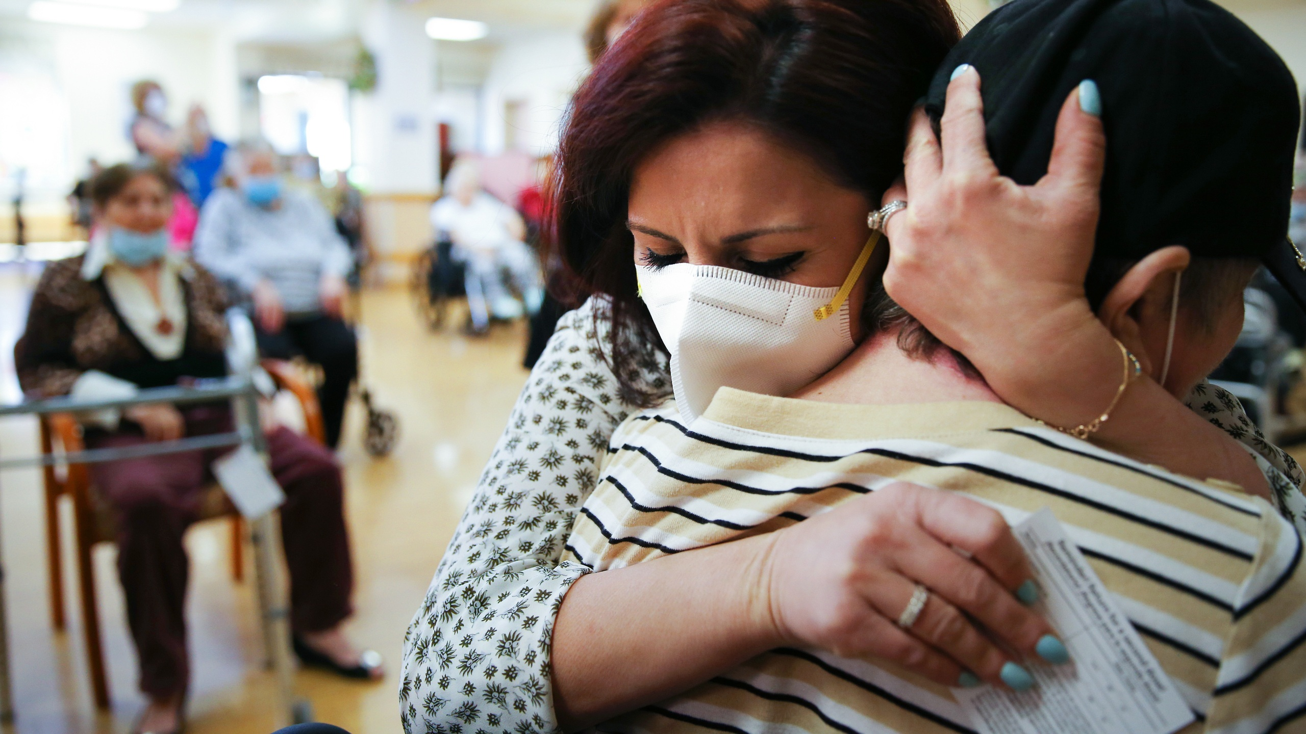 Executive director Margarita Kechichian, center, hugs a long-time resident during an Easter concert for vaccinated residents at the Ararat Nursing Facility in Mission Hills on April 1, 2021. (Mario Tama / Getty Images)