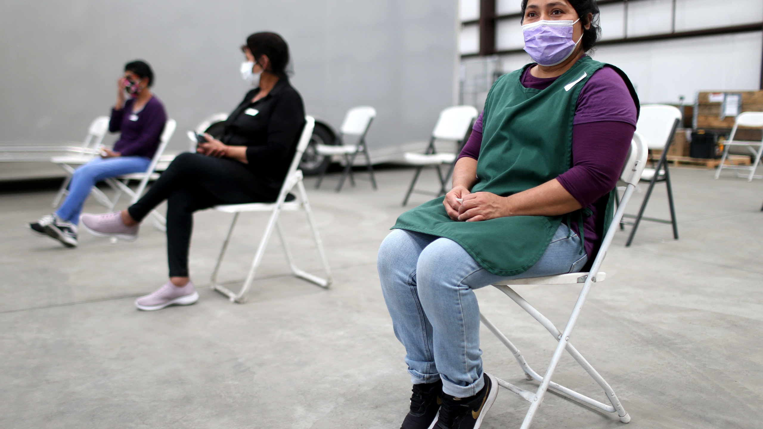 Workers sit in the observation area after receiving a one shot dose of the Johnson & Johnson COVID-19 vaccine at a clinic geared toward agriculture workers organized by TODEC on April 05, 2021 in Riverside, California. (Mario Tama/Getty Images)