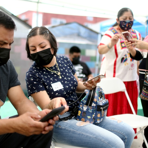 Volunteer Miriam Lopez Ambrosio (second from right) assists people with their vaccination appointments at a clinic on April 10, 2021, in Los Angeles. (Mario Tama/Getty Images)