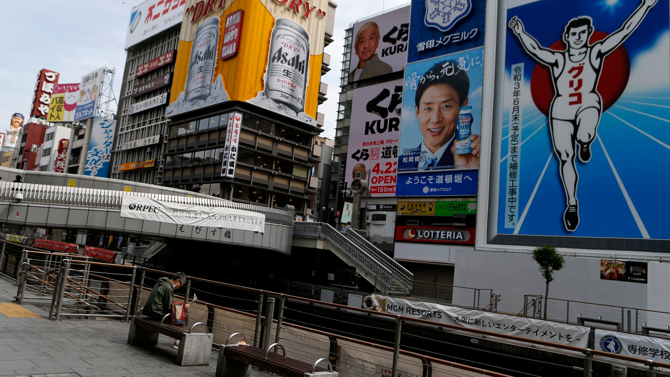 A man wearing protective face mask sits a bench at almost empty Dotonbori, one of Osaka's most popular tourist areas on April 23, 2021 in Osaka, Japan. (Buddhika Weerasinghe/Getty Images)