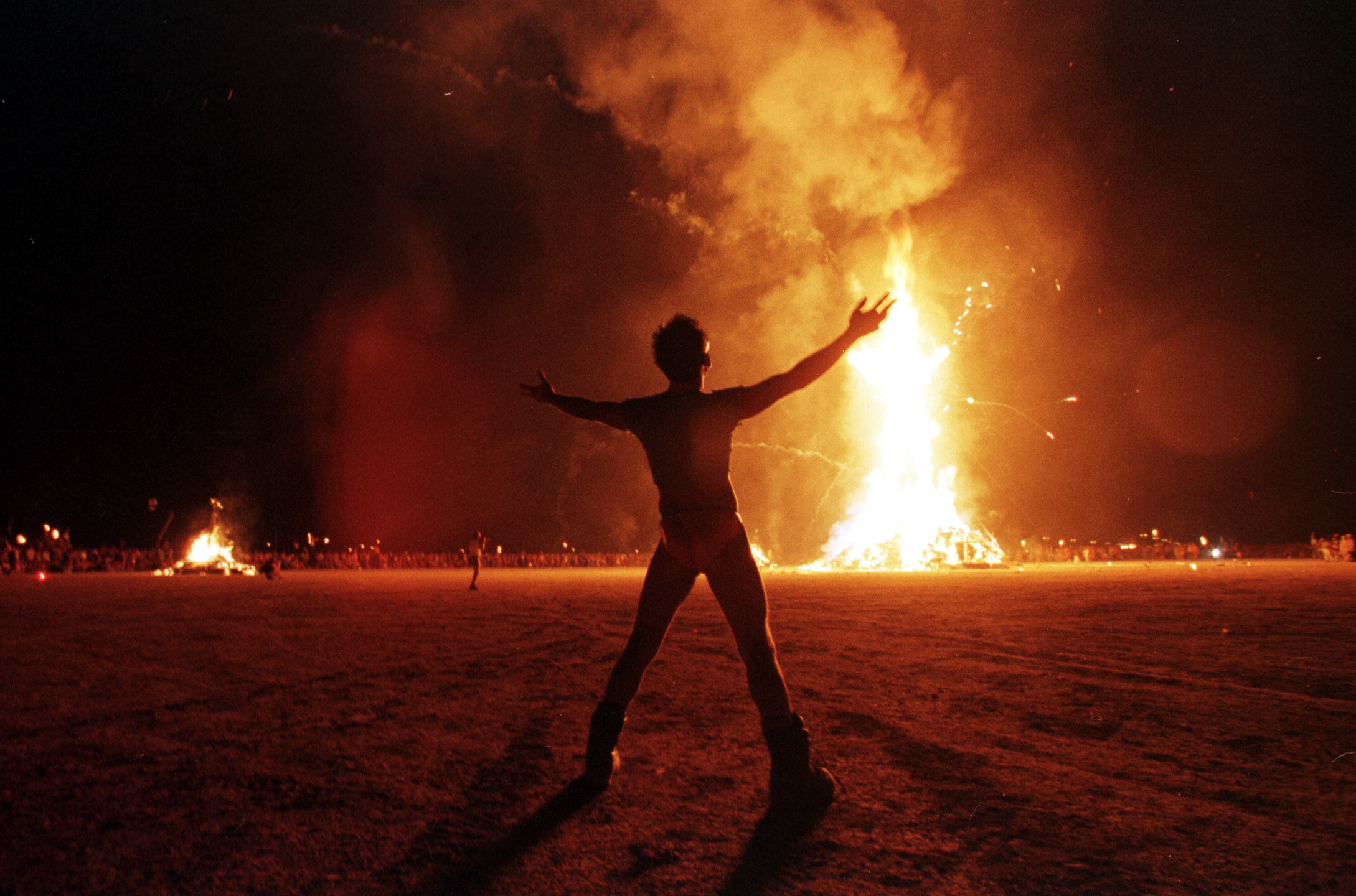 A Burning Man participant holds up his arms as the wooden man effigy is burned at the conclusion of the week-long festival on Sept. 6, 1998. (MIKE NELSON/AFP via Getty Images)