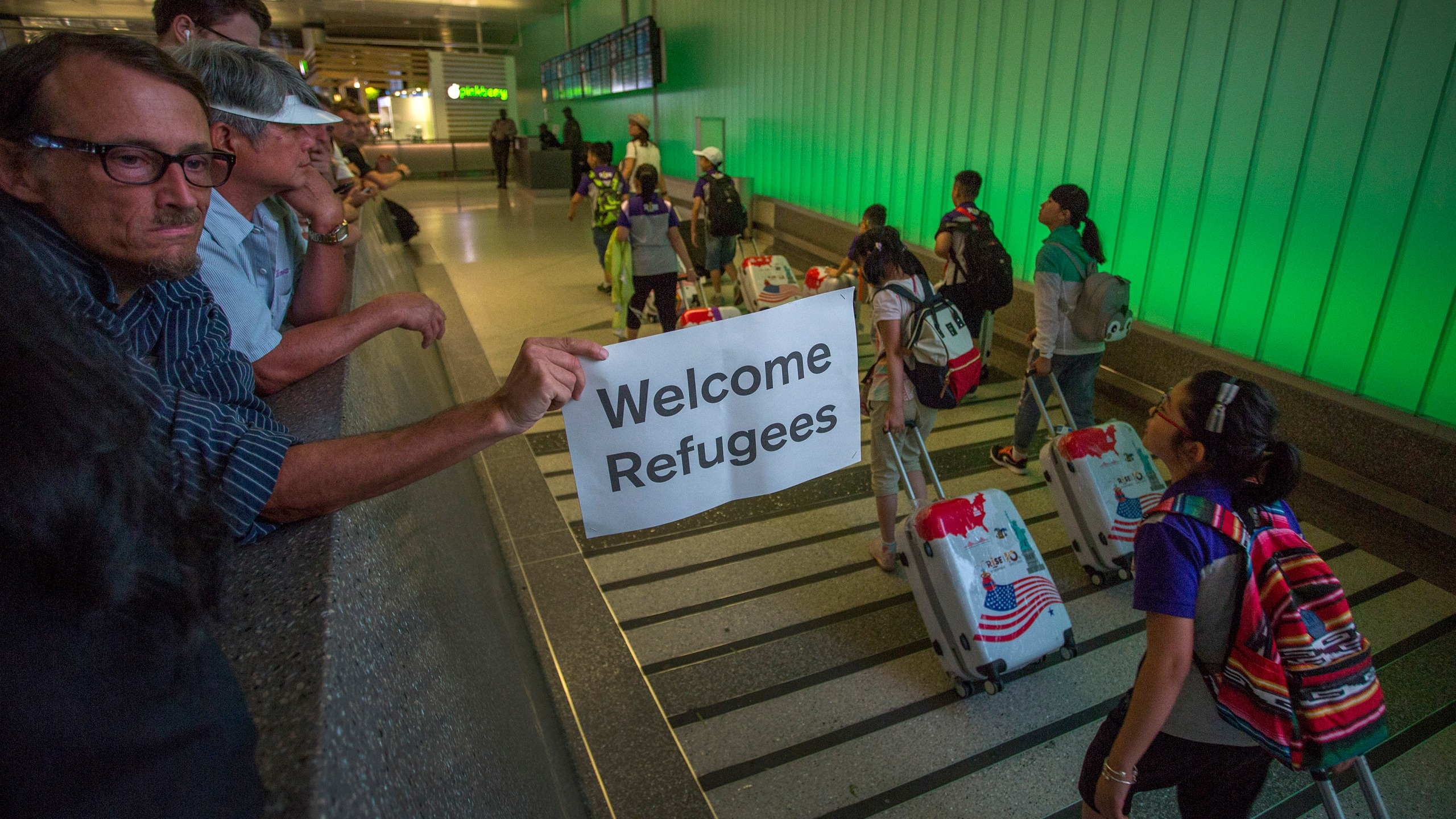 A man carries a welcome sign near arriving international travelers at LAX on the first day of the partial reinstatement of Trump's travel ban on June 29, 2017 in Los Angeles. (David McNew/Getty Images)