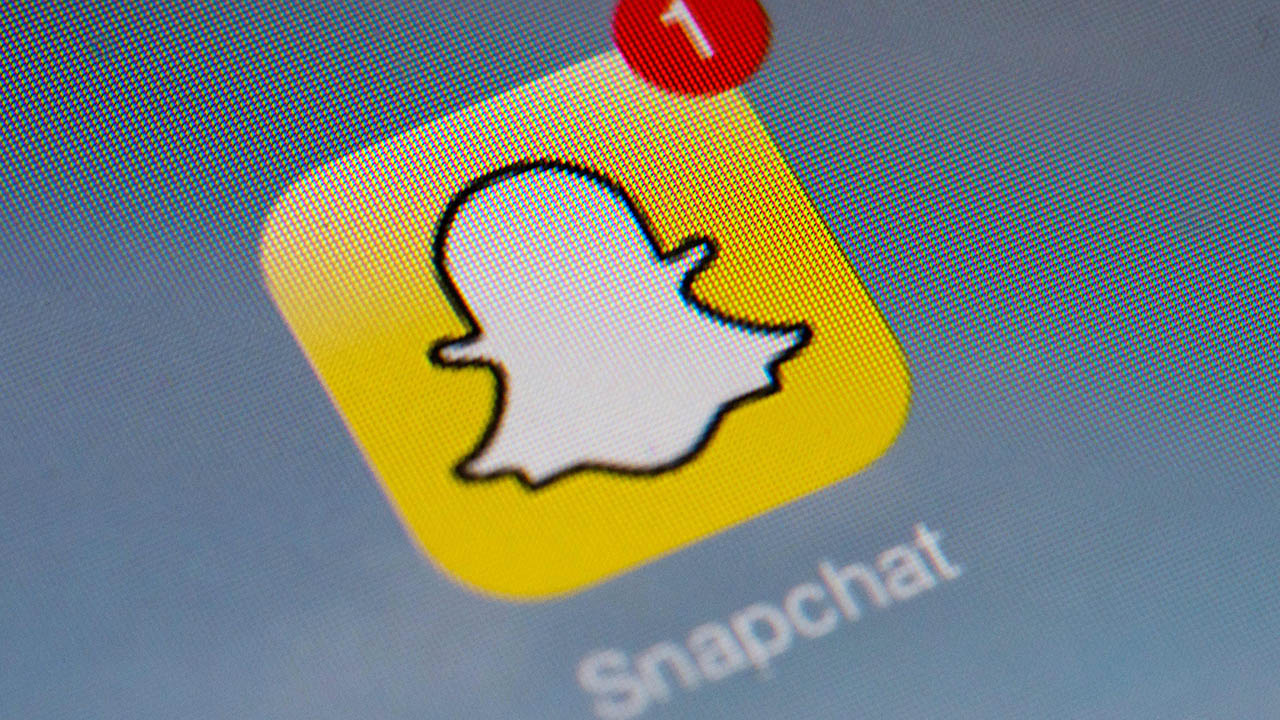 "The logo of mobile app ""Snapchat"" is displayed on a tablet on January 2, 2014 in Paris. (LIONEL BONAVENTURE/AFP via Getty Images)"