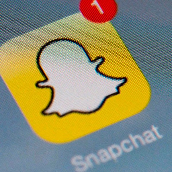 """The logo of mobile app """"Snapchat"""" is displayed on a tablet on January 2, 2014 in Paris. (LIONEL BONAVENTURE/AFP via Getty Images)"""