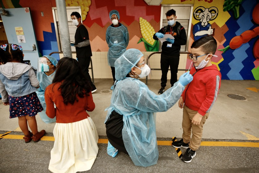 In April 2021, as LAUSD students go back to school for the first time in a year, kindergarten student Matteo Rodriguez, right, is tested for COVID-19 by medical technician Claire Chou before entering Heliotrope Avenue Elementary School. (Al Seib / Los Angeles Times)