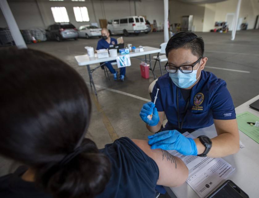 Registered nurse Justine Bertulano gives Yolanda Estrada-Saporito of Garden Grove her second dose of the Moderna COVID-19 vaccine Saturday in Gardena.(Francine Orr / Los Angeles Times)