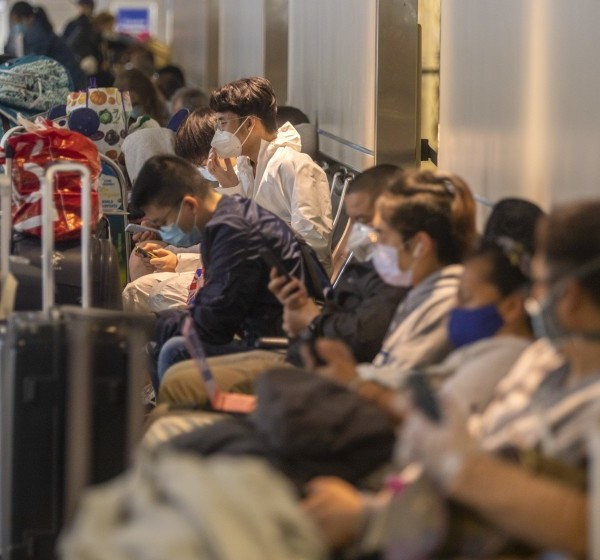 Travelers sit in a crowded waiting area Friday at Los Angeles International Airport. (Francine Orr / Los Angeles Times)