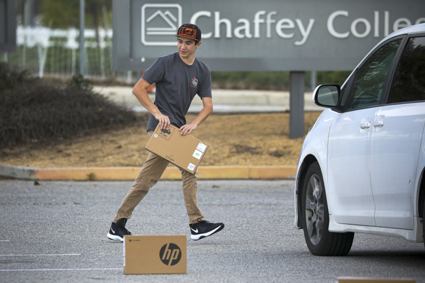Following social distancing measures, a student picks up a laptop placed in the parking lot of Chaffey College on March 25, 2020, at the Chino, Calif., campus. According a press release, Chaffey College lent about 5,000 laptops to students as it transitioned most classes online amid the pandemic. (Irfan Khan/Los Angeles Times)