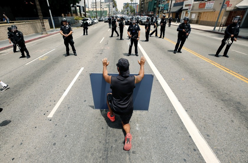 Protester Diego Martinez takes a knee in front of Los Angeles police officers in Hollywood on June 2, 2020. (Al Seib / Los Angeles Times)