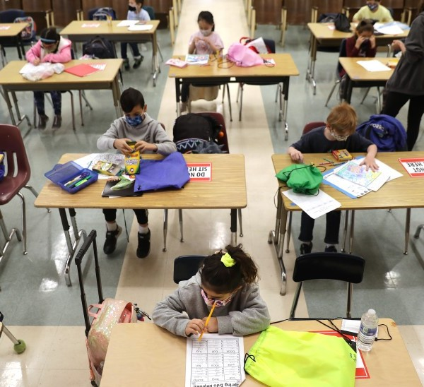 First-graders do schoolwork in the auditorium at Warner Avenue Elementary in Westwood on April 16. Warner Avenue was among 61 elementary and 11 early-education L.A. Unified campuses that opened last week for the first time in over a year.(Christina House / Los Angeles Times)