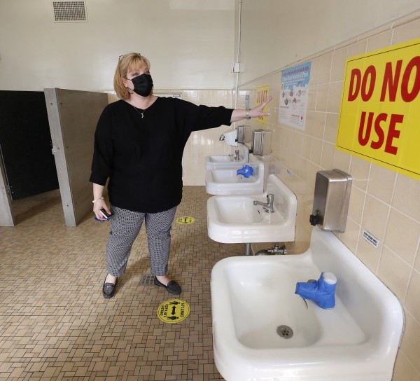 Social distancing will be in place when L.A. campuses begin to reopen this week, including in the bathrooms at West Hollywood Elementary. Principal Elizabeth Lehmann shows how alternating sinks and stalls will be shut.(Al Seib / Los Angeles Times)