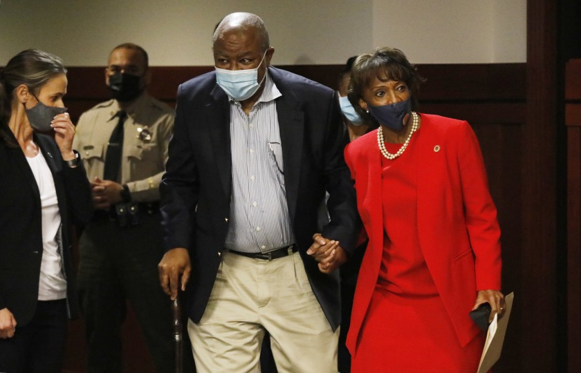 Then-Los Angeles County Dist. Atty. Jackie Lacey holds hands with her husband, David, on the way to a news conference after her defeat at the polls in November. (Al Seib / Los Angeles Times)