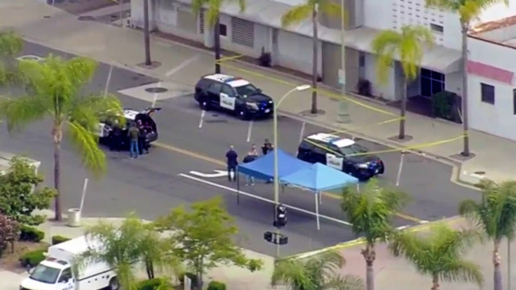 """Investigators work at the scene of a police shooting in Escondido, where officials say an officer shot a man who had been seen with a """"large metal object,"""" but shared few further details."""
