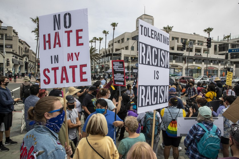 Protesters gather on Sunday in Huntington Beach. (Brian van der Brug/Los Angeles Times)