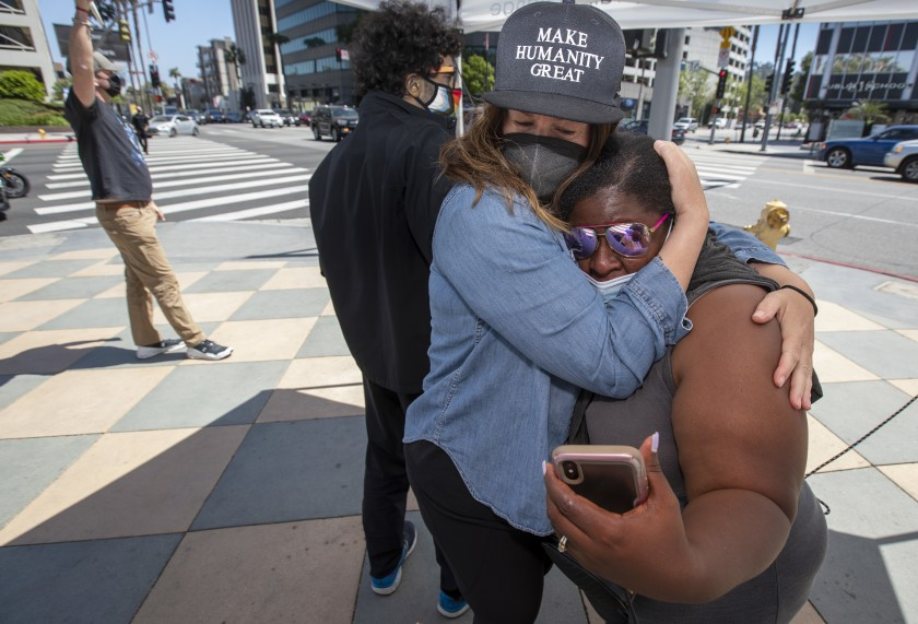 Katie Mau, left, embraces Latora Green in Sherman Oaks as the verdicts are read in the Derek Chauvin trial on April 20, 2021. Green has been standing in front of the Sherman Oaks Galleria on Ventura and Sepulveda boulevards for 325 straight days. (Brian van der Brug / Los Angeles Times)
