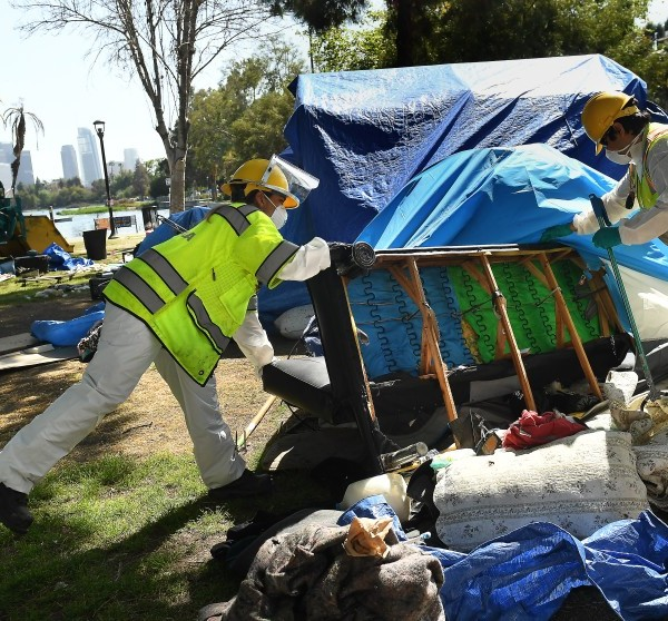Workers remove a couch from a campsite left behind by a homeless person in Echo Park in April 2021. (Wally Skalij / Los Angeles Times)