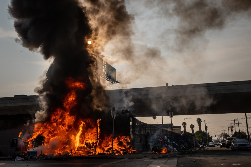 A homeless encampment burns at South Grand Avenue and West 54th Street, next to the 110 Freeway, in October 2020. (Jay L. Clendenin / Los Angeles Times)