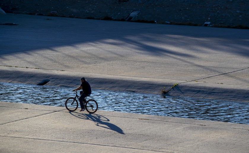 A cyclist rides along the Los Angeles River in South Gate in an undated photo. (Brian van der Brug / Los Angeles Times)