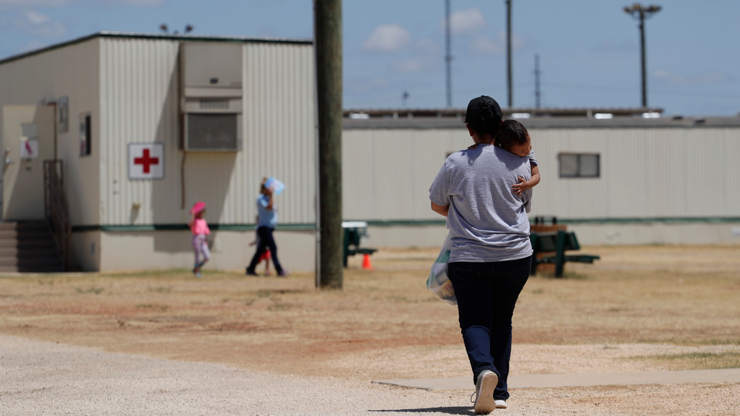 Immigrants seeking asylum walk at the ICE South Texas Family Residential Center, Friday, Aug. 23, 2019, in Dilley, Texas. (AP Photo/Eric Gay, File)