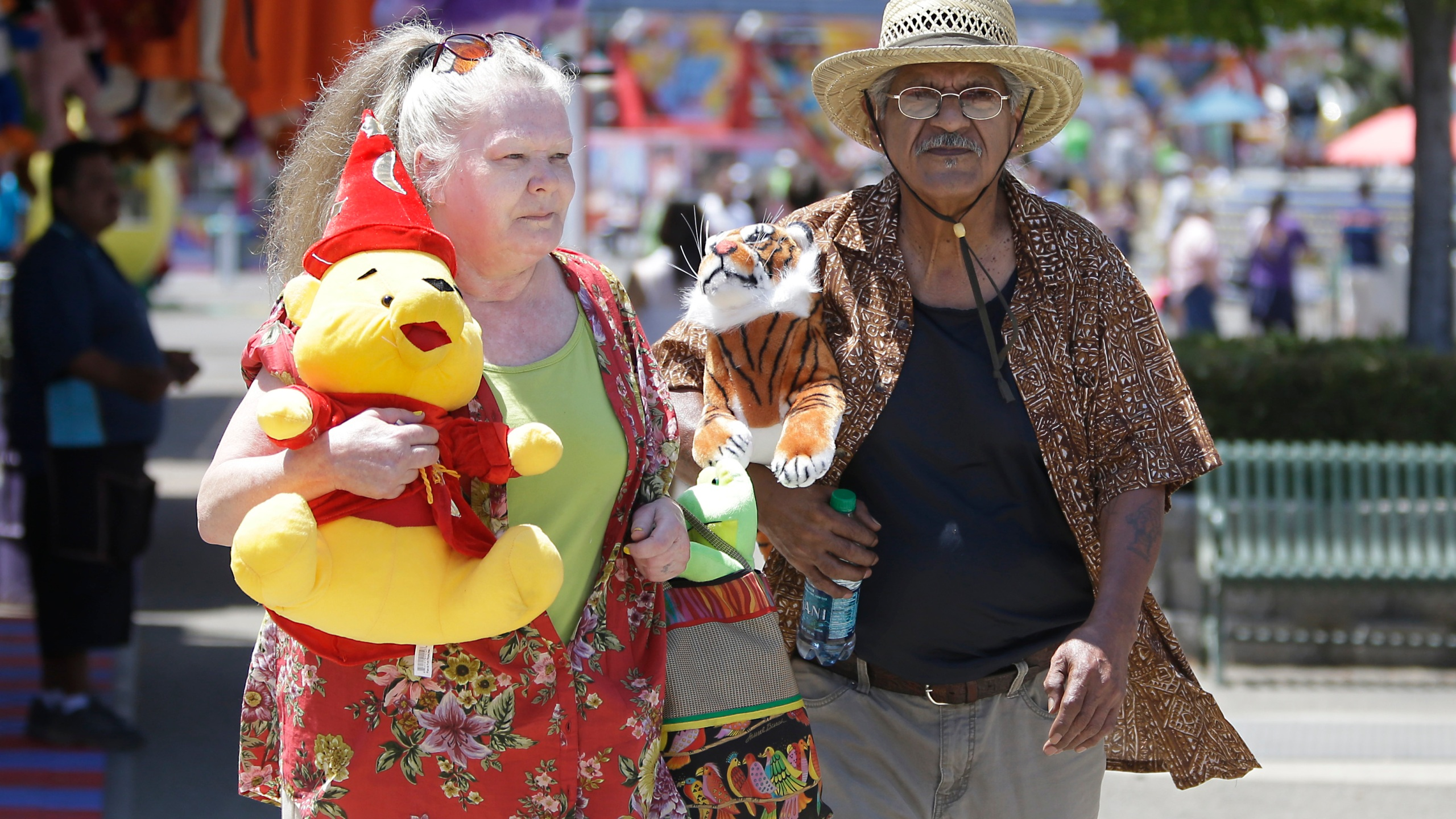 Joanne Hayes and Walter DeLaGarza carry their prizes won at one of the carnival games at the California State Fair on July 10, 2015, in Sacramento, Calif. (AP Photo/Rich Pedroncelli)