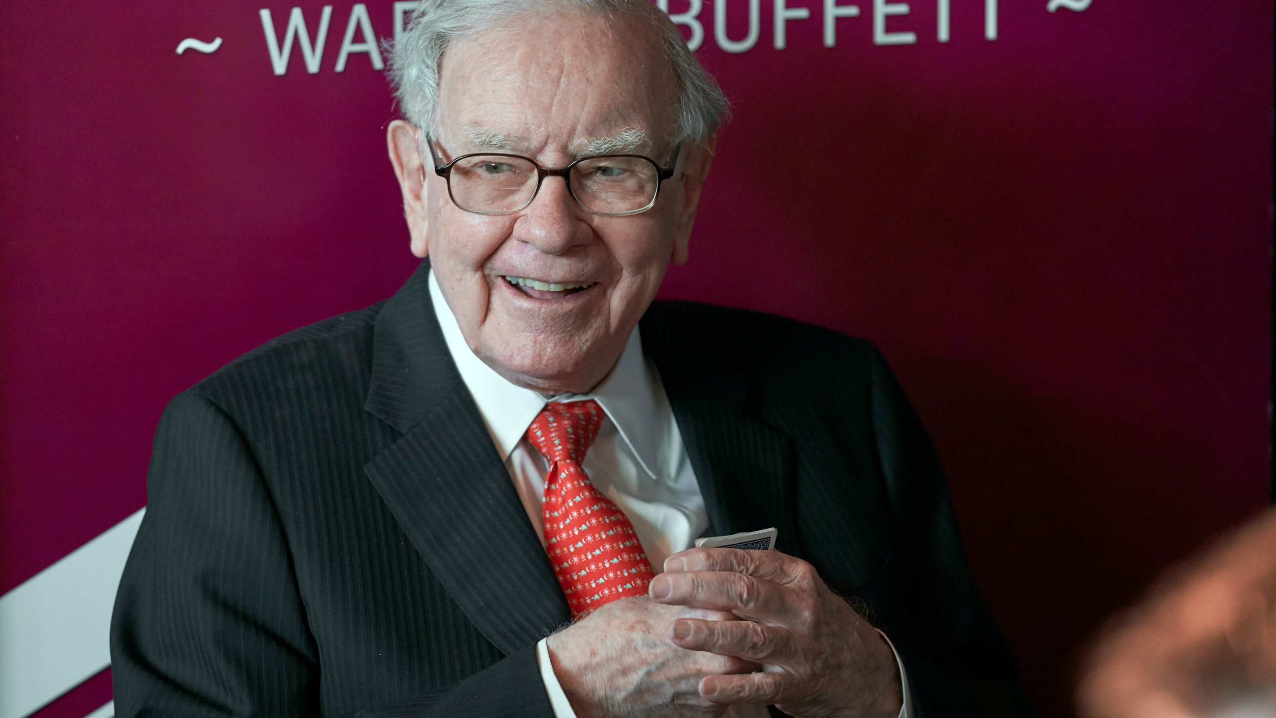 In this May 5, 2019, file photo Warren Buffett, Chairman and CEO of Berkshire Hathaway, smiles as he plays bridge following the annual Berkshire Hathaway shareholders meeting in Omaha, Neb. Buffett will spend Saturday afternoon fielding questions at Berkshire Hathaway's annual meeting, which is being held virtually. (AP Photo/Nati Harnik, File)