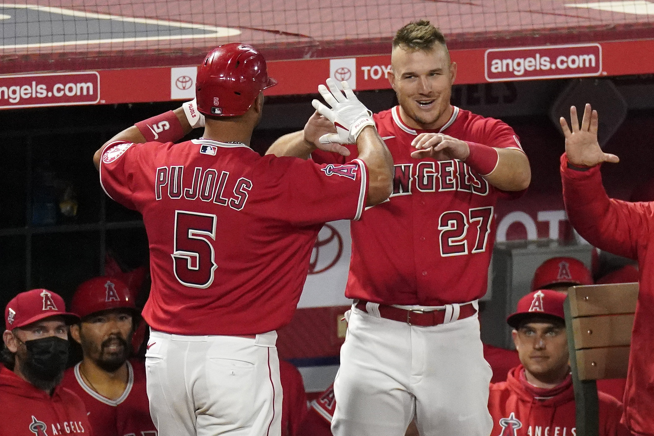 Los Angeles Angels' Albert Pujols, left, is congratulated by Mike Trout after hitting a solo home run during the seventh inning of a baseball game against the Texas Rangers in Anaheim on April 20, 2021. (Mark J. Terrill / Associated Press)