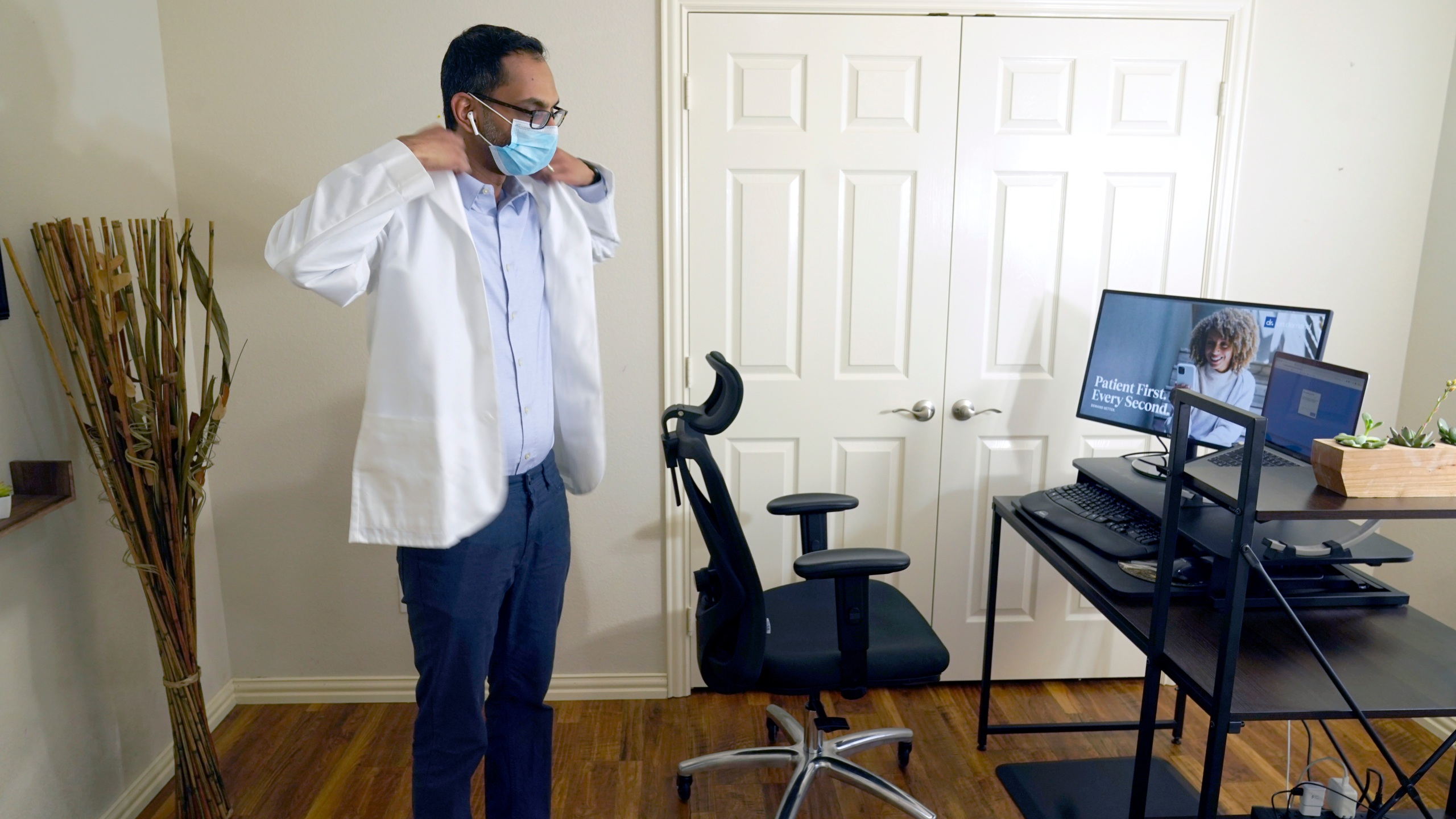 Medical director of Doctor on Demand Dr. Vibin Roy prepares to conduct an online visit with a patient from his work station at home, Friday, April 23, 2021, in Keller, Texas. (AP Photo/LM Otero)