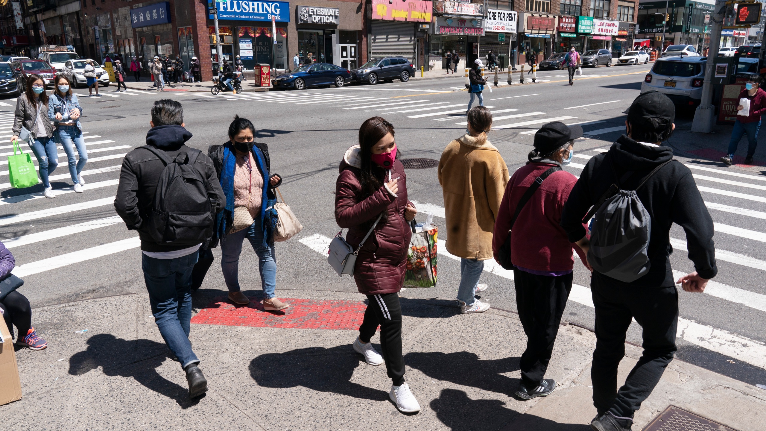People walk on the street on April 26, 2021, in New York. (Mark Lennihan / Associated Press)