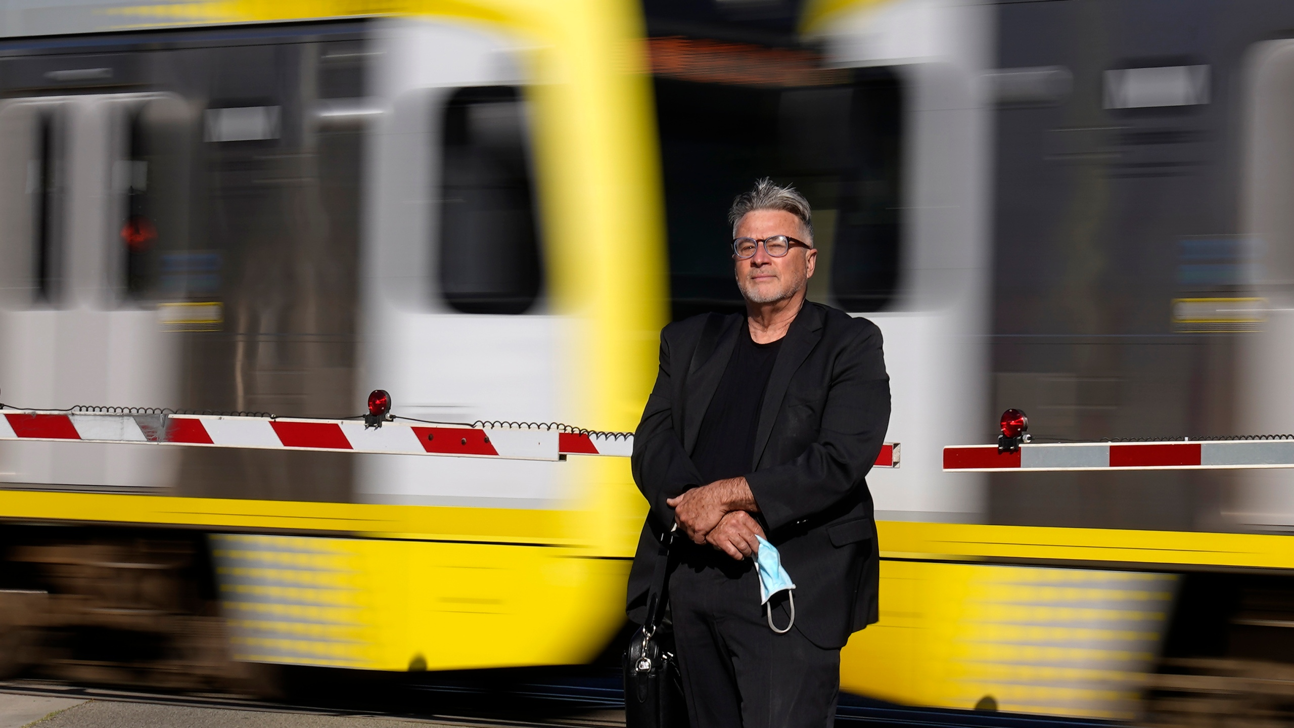 In this April 27, 2021, photo Brad Hudson poses as a Los Angeles Metro train goes by in South Pasadena, Calif. (AP Photo/Mark J. Terrill)