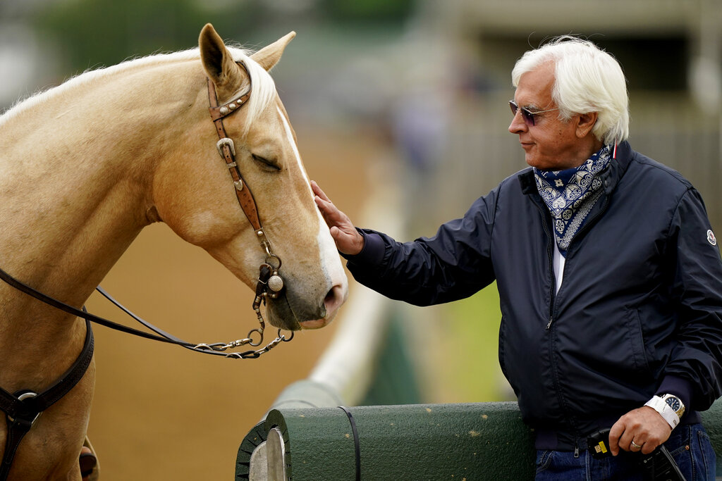 Trainer Bob Baffert pets an outrider's horse while watching workouts at Churchill Downs Wednesday, April 28, 2021, in Louisville, Ky. The 147th running of the Kentucky Derby is scheduled for Saturday, May 1. (AP Photo/Charlie Riedel)