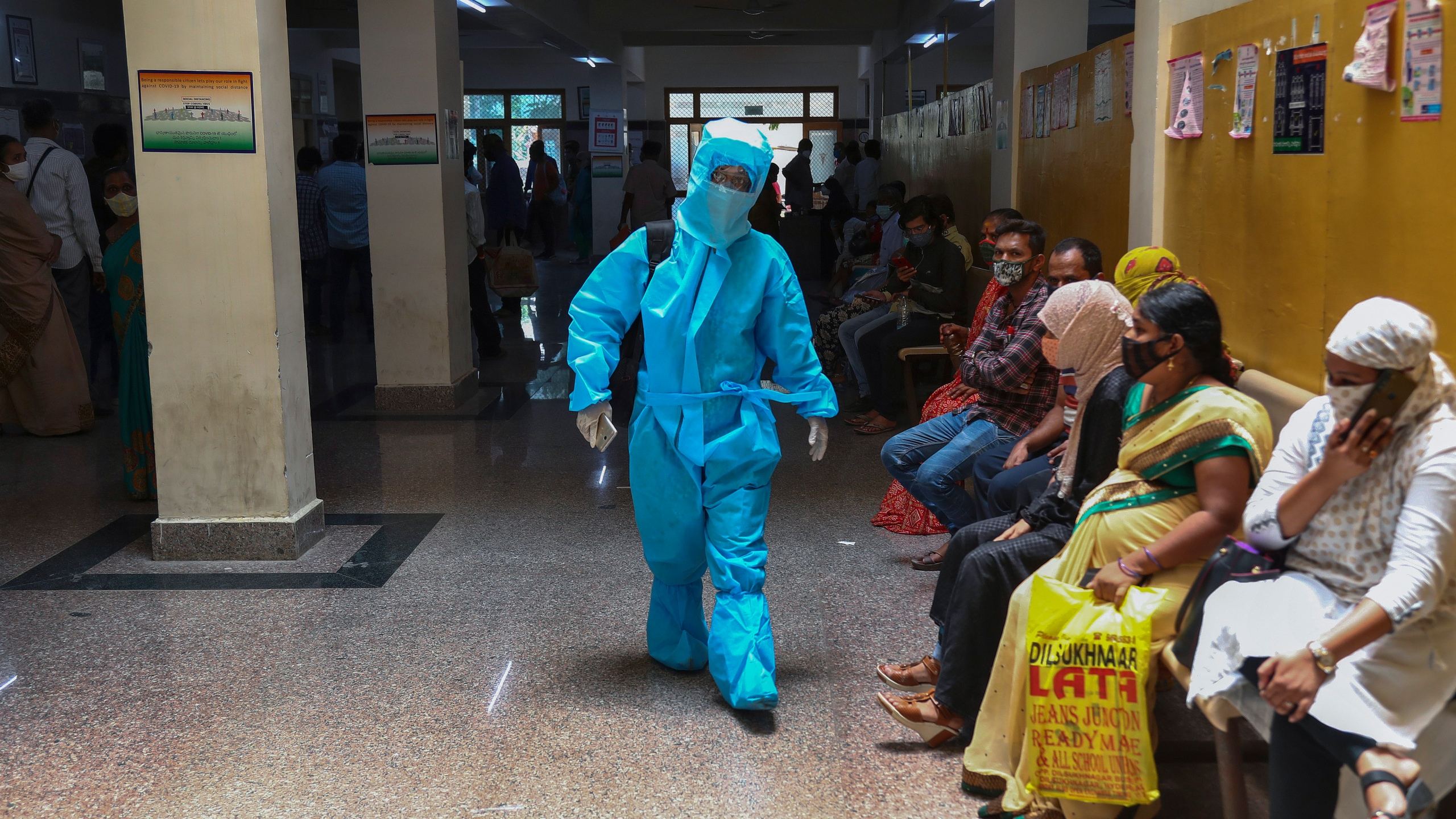 An Indian woman in personal protective suit walks towards a COVID-19 ward of a hospital as others waits for their test results in Hyderabad, India, Thursday, April 29, 2021. (AP Photo/Mahesh Kumar A.)