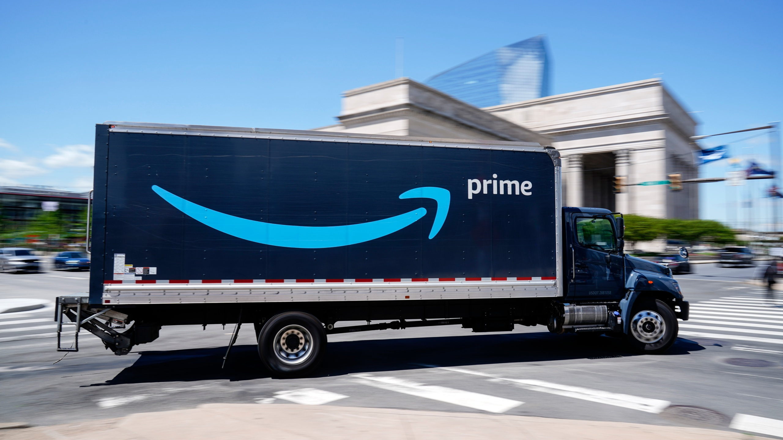An Amazon truck drives in in Philadelphia, Friday, April 30, 2021. Amazon is seeking to hire 75,000 people in a tight job market and is offering bonuses to attract workers, including $100 for new hires who are already vaccinated for COVID-19. (AP Photo/Matt Rourke)