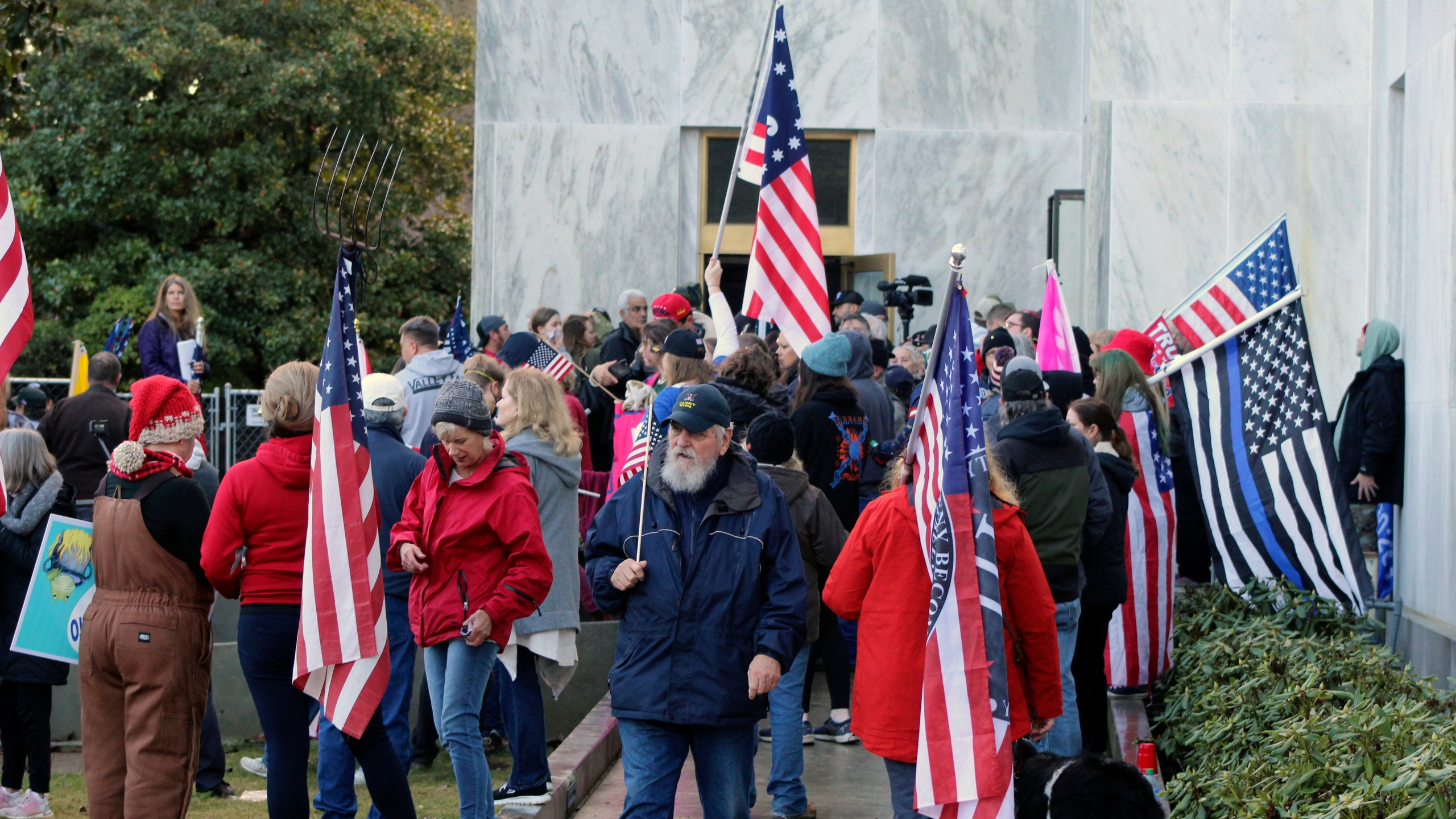 In this Dec. 21, 2020, file photo, pro-Trump and anti-mask demonstrators hold a rally outside the Oregon State Capitol as legislators meet for an emergency session in Salem, Ore. Prosecutors leveled two criminal charges Friday, April 30, 2021, against a Republican member of the Oregon House of Representatives who let far-right rioters into the state Capitol that day. Rep. Mike Nearman was charged with official misconduct in the first degree and criminal trespass in the second degree. (AP Photo/Andrew Selsky, File)