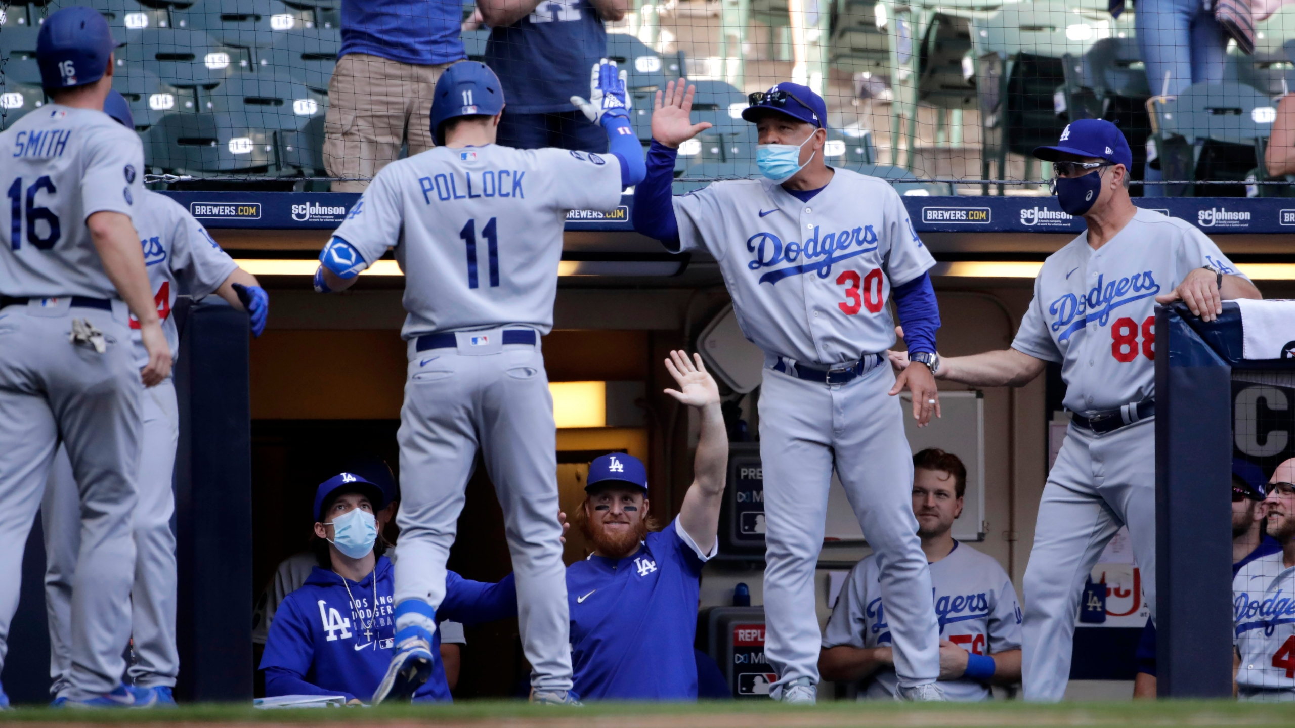 Los Angeles Dodgers' AJ Pollock (11) is congratulated by manager Dave Roberts (30) after hitting a three-run home run during the sixth inning of a baseball game against the Milwaukee Brewers, Sunday, May 2, 2021, in Milwaukee. (AP Photo/Aaron Gash)
