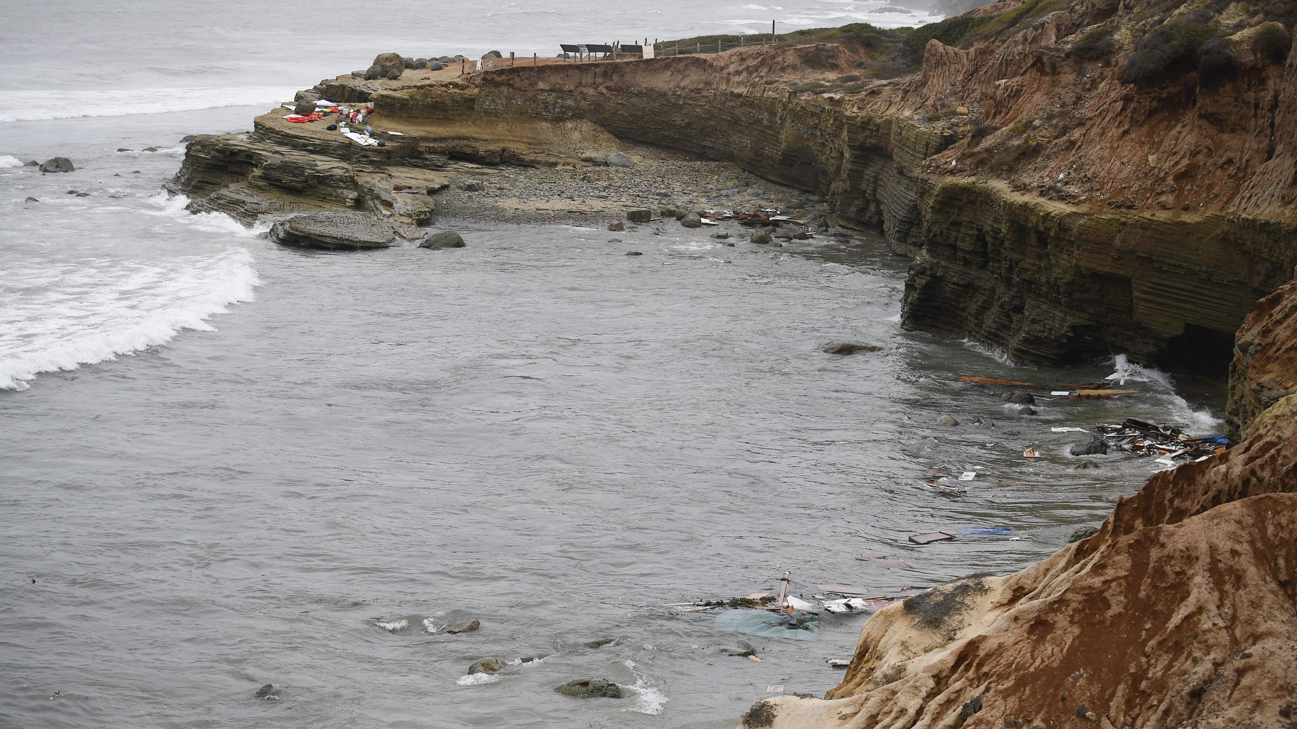 Wreckage and debris from a capsized boat washes ashore at Cabrillo National Monument near where a boat capsized just off the San Diego coast on May 2, 2021. (Denis Poroy / Associated Press)