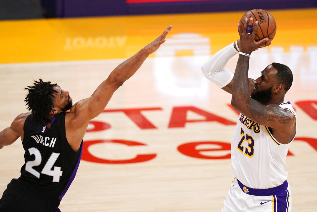 Los Angeles Lakers forward LeBron James, right, shoots as Toronto Raptors center Khem Birch defends during the first half of an NBA basketball game Sunday, May 2, 2021, in Los Angeles. (AP Photo/Mark J. Terrill)