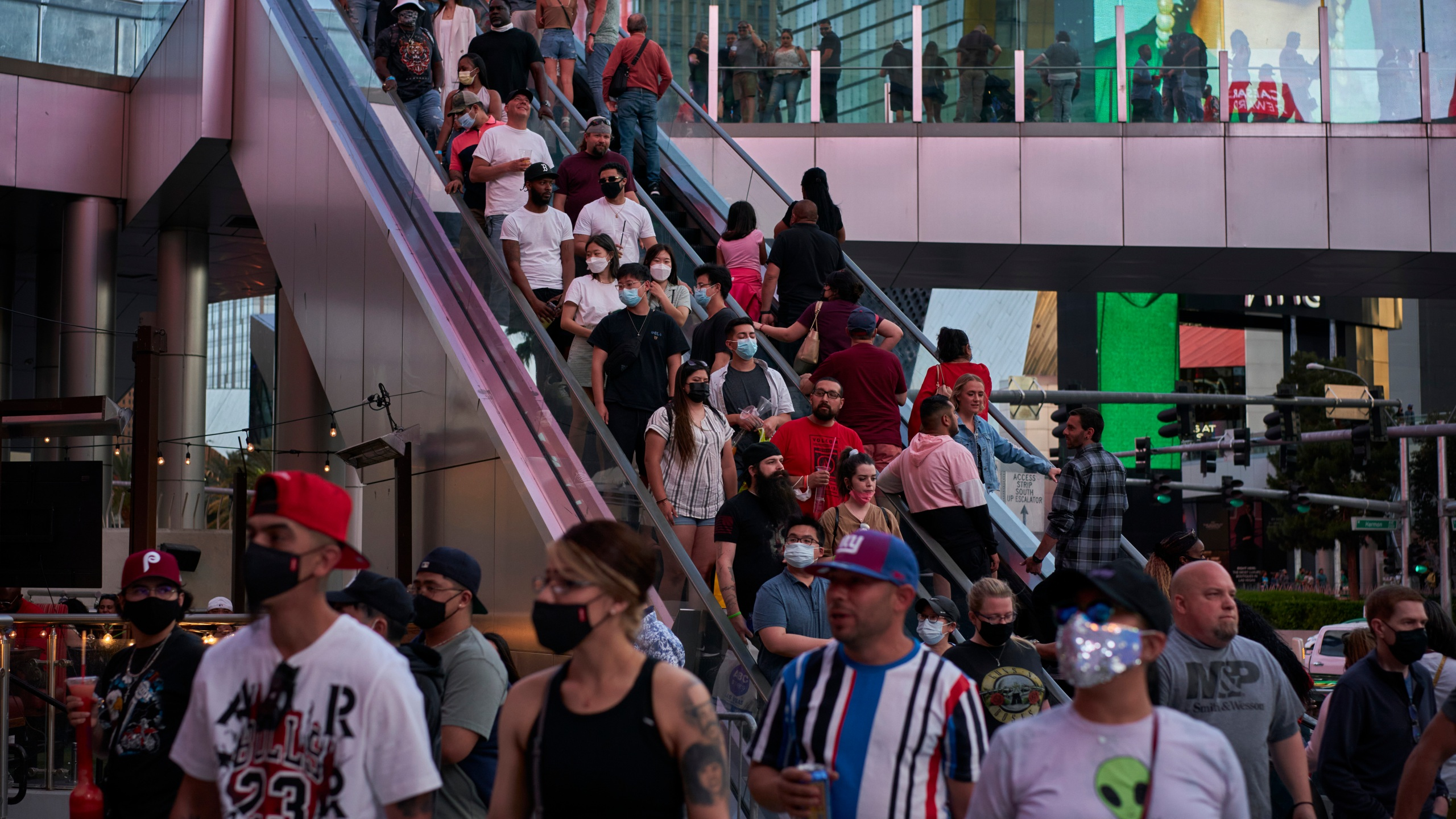 People ride an escalator along the Las Vegas Strip, Saturday, April 24, 2021, in Las Vegas. The tourism-dependent city is bustling again after casino capacity limits were raised Saturday, May 1, to 80% and person-to-person distancing dropped to 3 feet (0.9 meters). (AP Photo/John Locher)
