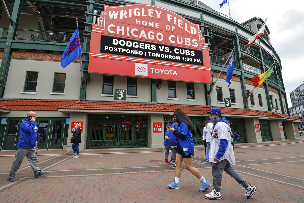 Fans walk outside Wrigley Field as a baseball game between the Chicago Cubs and the Los Angels Dodgers was postponed due to the forecast of inclement weather, Monday, May 3, 2021, in Chicago. (AP Photo/Kamil Krzaczynski)