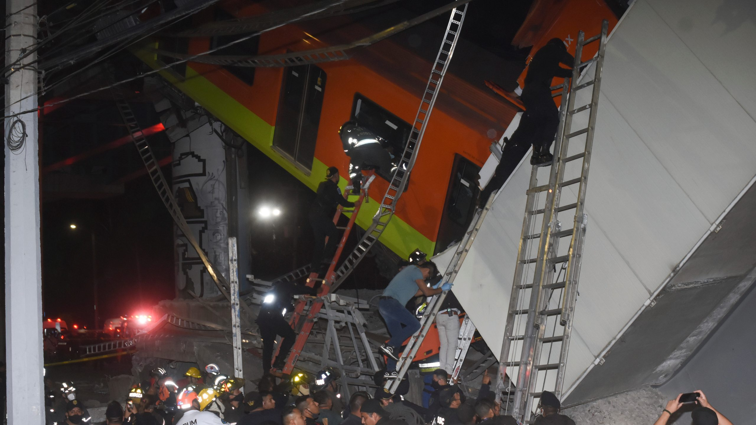 Mexico City firefighters and rescue personnel work to recover victims from a subway car that fell after a section of Line 12 of the subway collapsed in Mexico City on May 3, 2021. (Jose Ruiz/Associated Press)