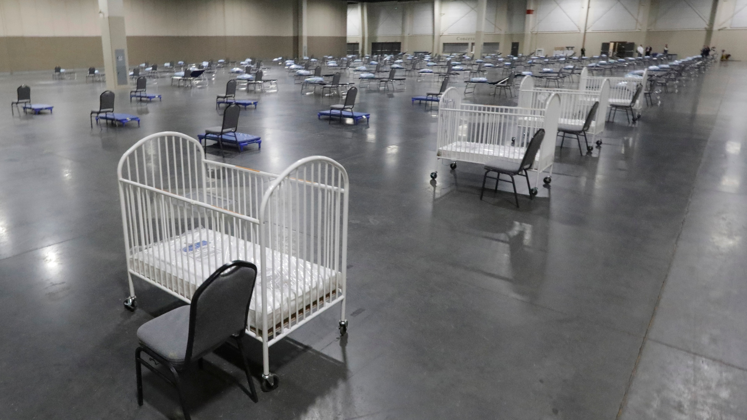 In this April 6, 2020, file photo, cots and cribs are arranged at the Mountain America Expo Center in Sandy, Utah, as an alternate care site or for hospital overflow amid the COVID-19 pandemic.(AP Photo/Rick Bowmer)