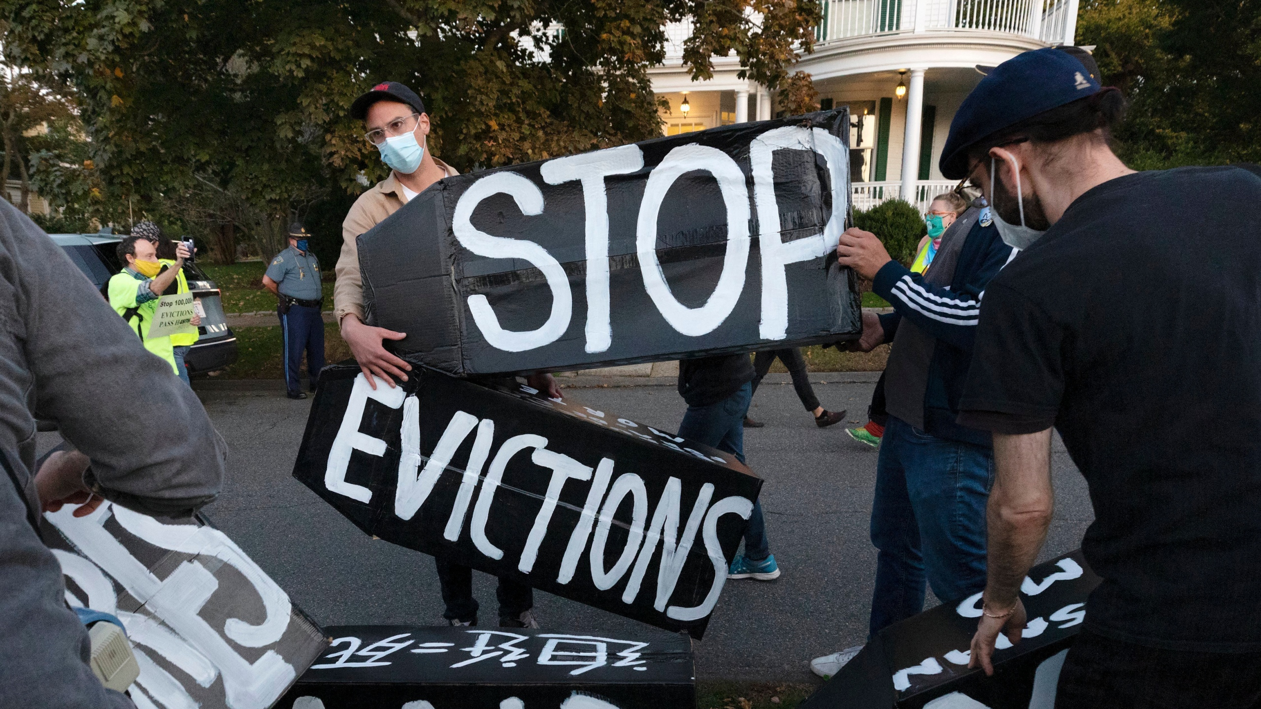 In this Oct. 14, 2020, file photo, housing activists erect a sign in front of Massachusetts Gov. Charlie Baker's house in Swampscott, Mass. (AP Photo/Michael Dwyer, File)