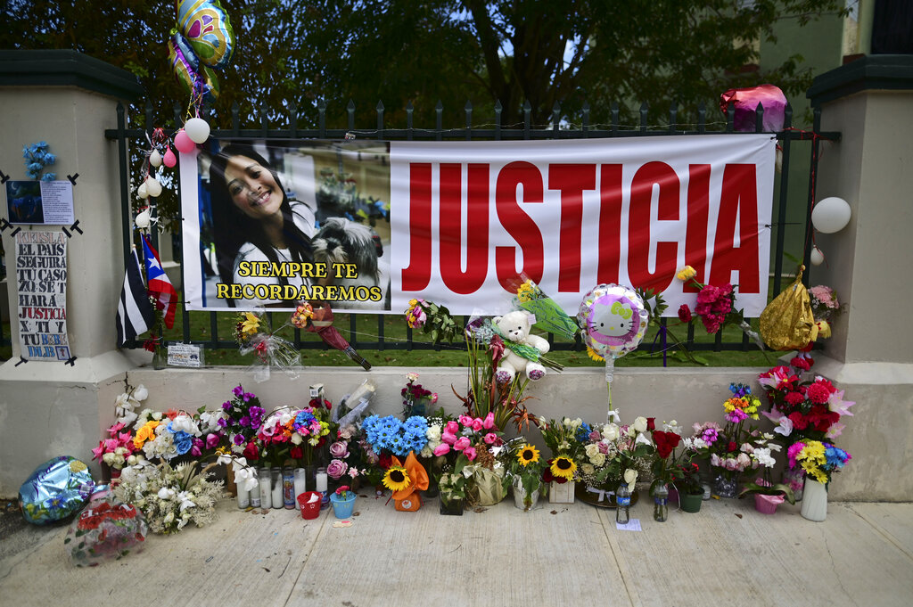 "Flowers, balloons and a poster with the Spanish word for ""justice"" is part of a growing makeshift memorial for Keishla Rodriguez whose lifeless body was found in a lagoon Saturday, at the entrance of where she lived in San Juan, Puerto Rico, Thursday, May 6, 2021. (AP Photo/Carlos Giusti)"