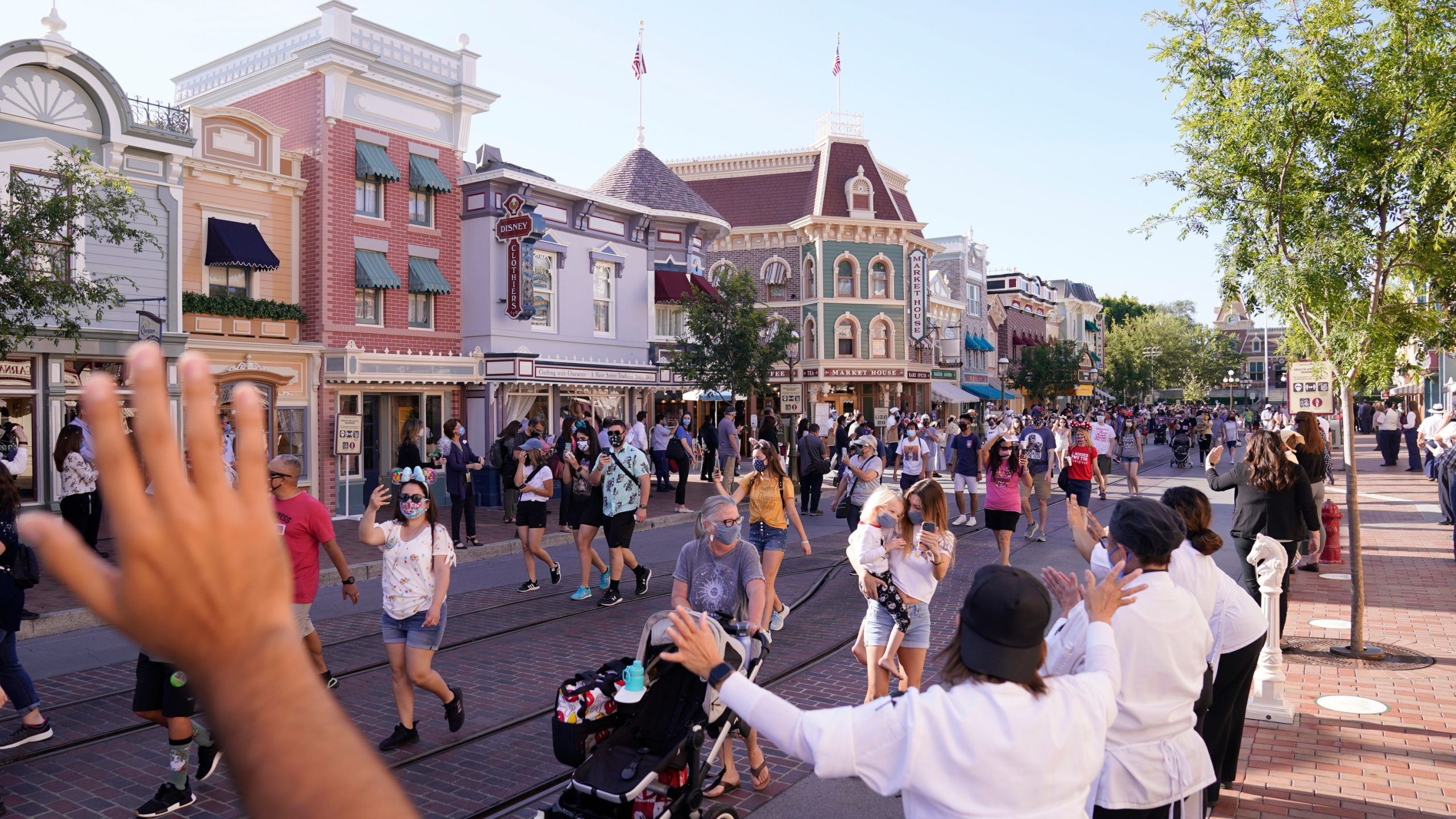 In this April 30, 2021, file photo, guests walk down Main Street USA at Disneyland in Anaheim. Los Angeles and San Francisco are reopening more businesses under California's least restrictive coronavirus safety rules, even though they have more infections than many other big counties, state data shows. (AP Photo/Jae Hong, File)