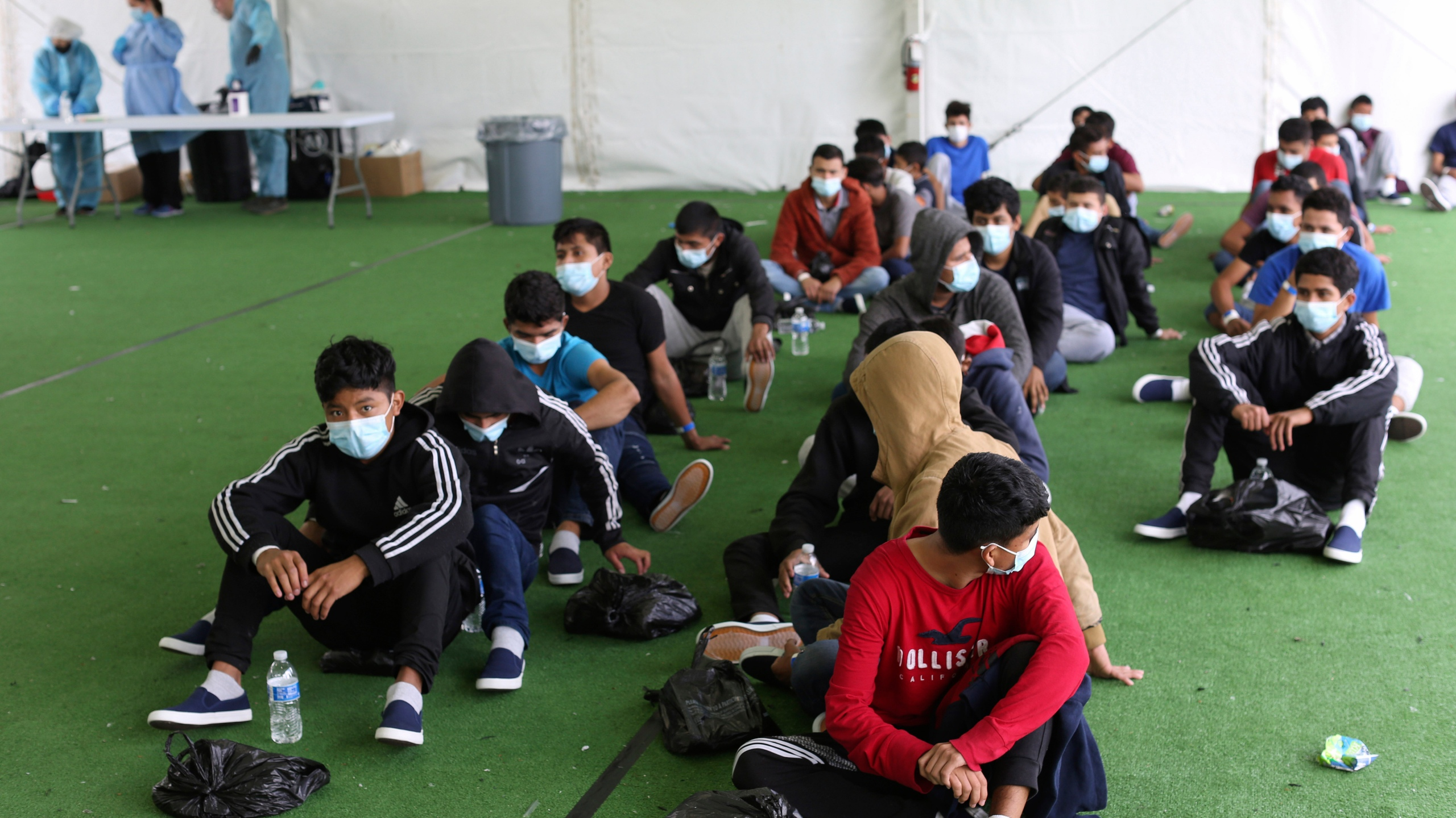 In this March 30, 2021 file photo, young migrants wait to be tested for COVID-19 at the Donna Department of Homeland Security holding facility, the main detention center for unaccompanied children in the Rio Grande Valley, in Donna, Texas. (AP Photo/Dario Lopez-Mills, Pool, File)