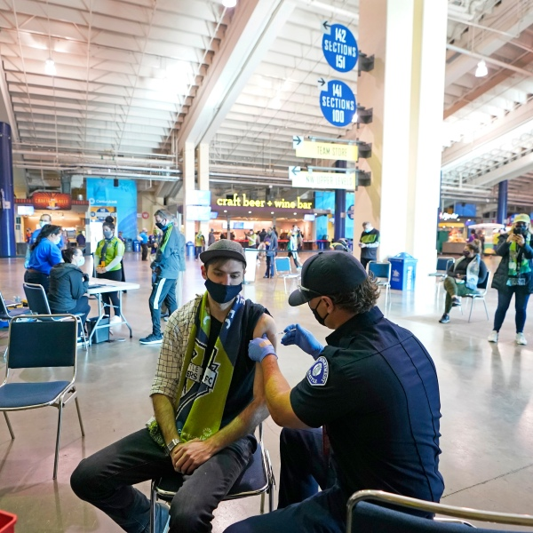 In this May 2, 2021, file photo, Austin Kennedy, left, a Seattle Sounders season ticket holder, gets the Johnson & Johnson COVID-19 vaccine at a clinic in a concourse at Lumen Field prior to an MLS soccer match between the Sounders and the Los Angeles Galaxy. (AP Photo/Ted S. Warren, File)